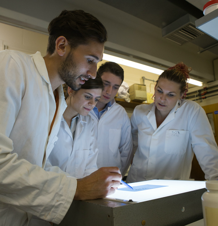 Four researchers in white lab coats looking at a screen