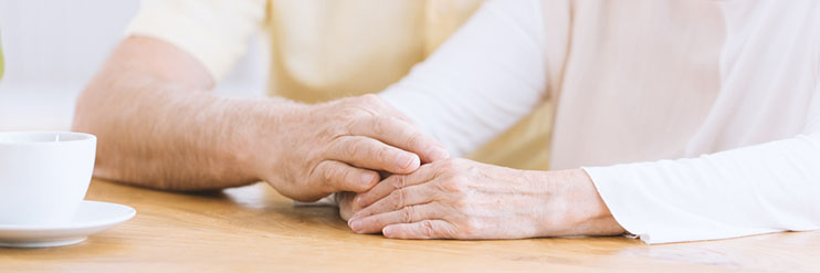 A close up of a couple holding hands on a table top