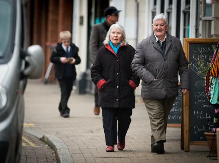 A man and woman walking down a high street