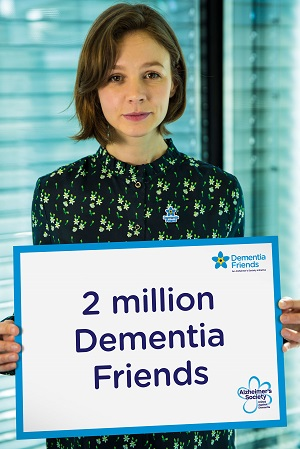 Carrey Mulligan holding a sign that says '2 million dementia friends'