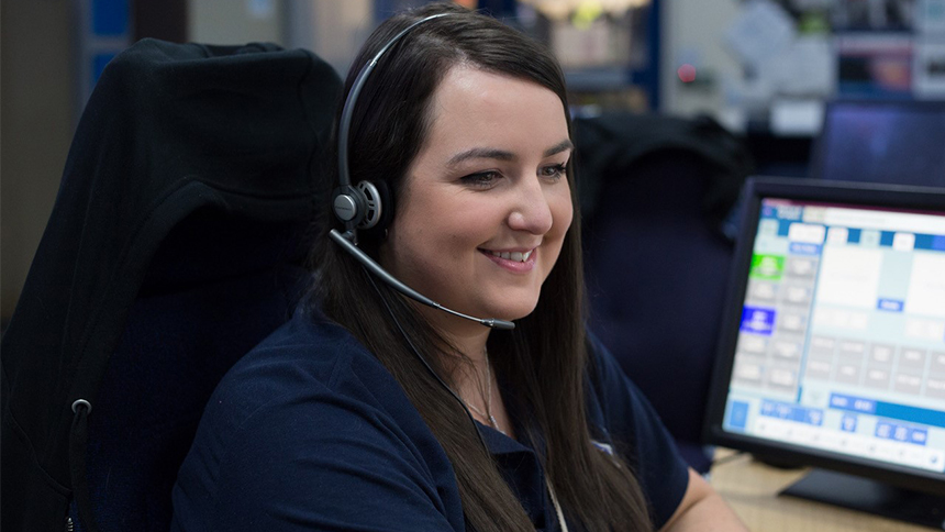 A woman sitting at an emergency call center desk