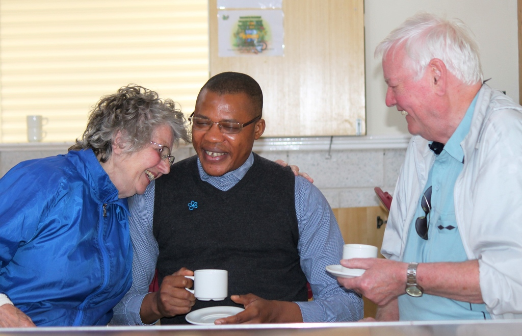Three people holding tea and laughing