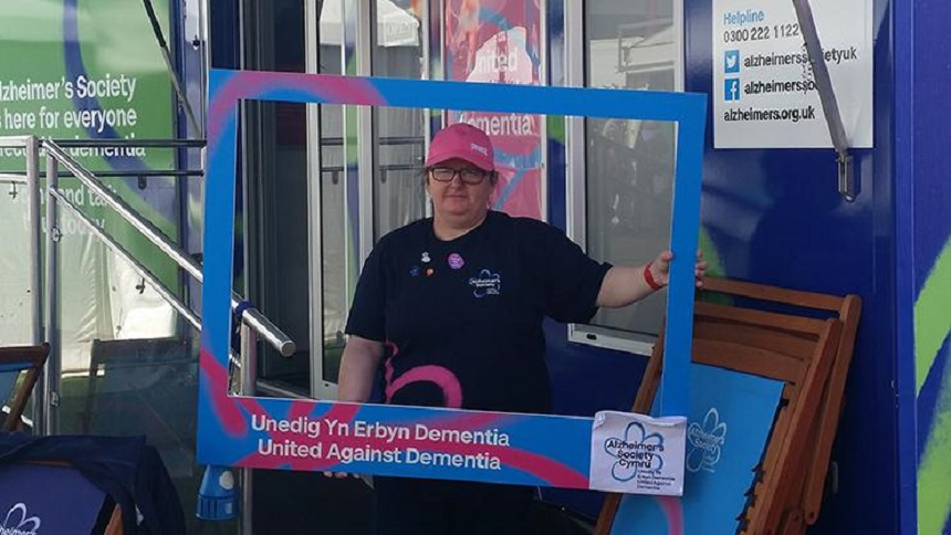Ceri Higgins holding up a blue Alzheimer's Society frame