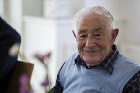 Man with dementia smiling. He has twinkling eyes.