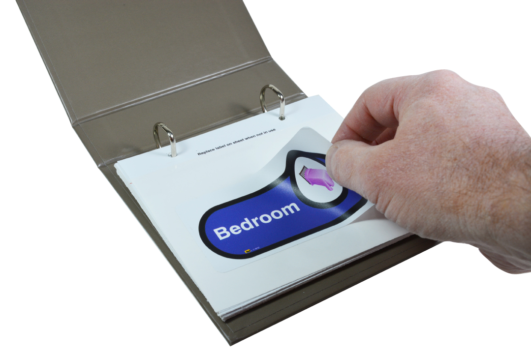 A hand unsticking a self-adhesive 'bedroom' sign