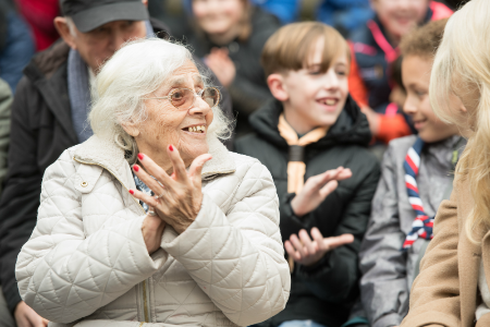 Woman with dementia clapping with group of Scouts