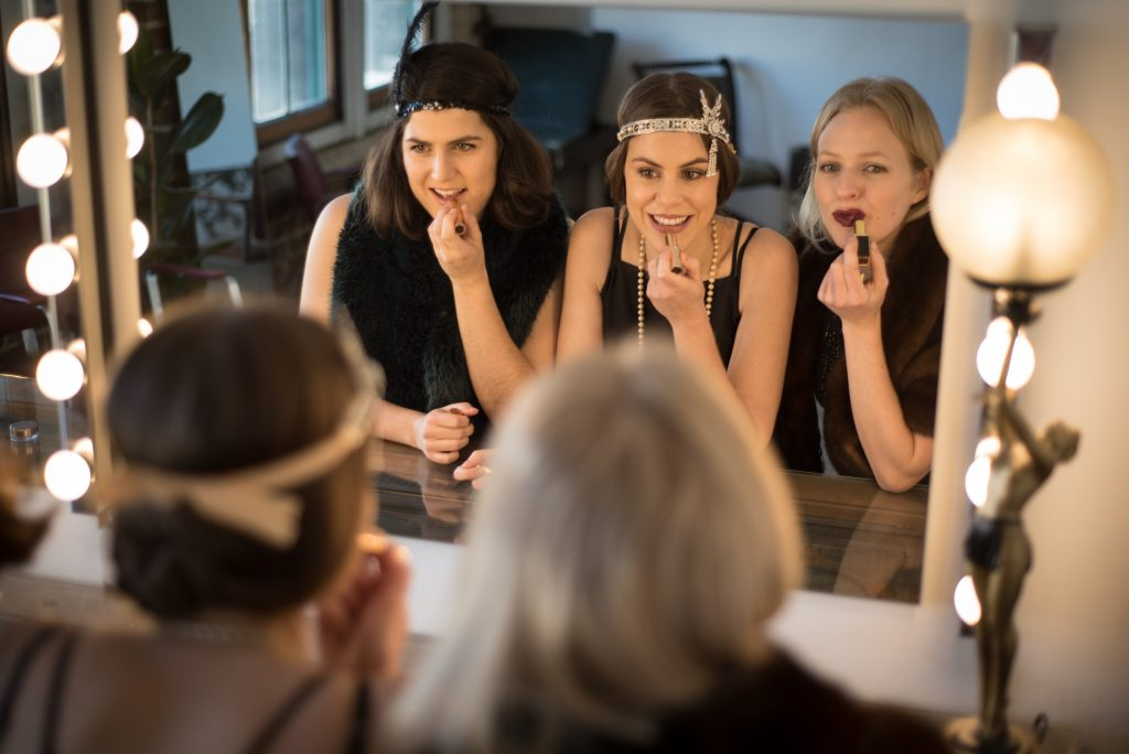 Three women wearing 20s clothes and putting on lipstick in the mirror for Flashback