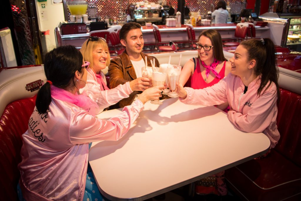 Four people drinking smoothies in a 1950s american diner to celebrate Flashback