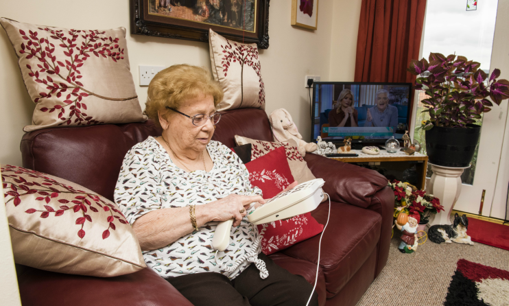 Women living with dementia making a call on her sofa.