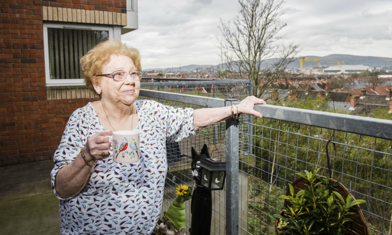 Dementia and social care: Woman with a cup of tea on a balcony.