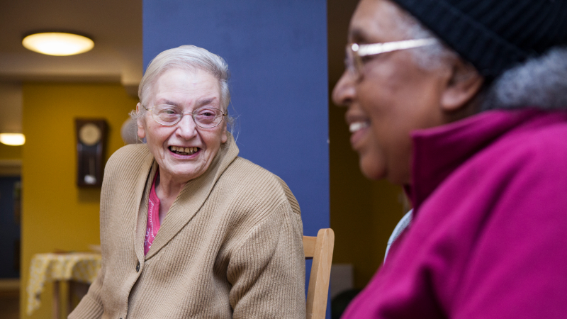 Two elder women smiling in conversation