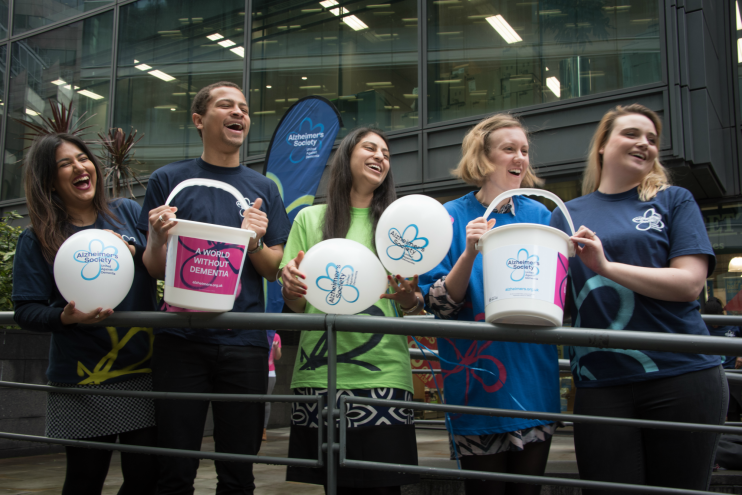 Alzheimer's Society fundraisers with donation buckets