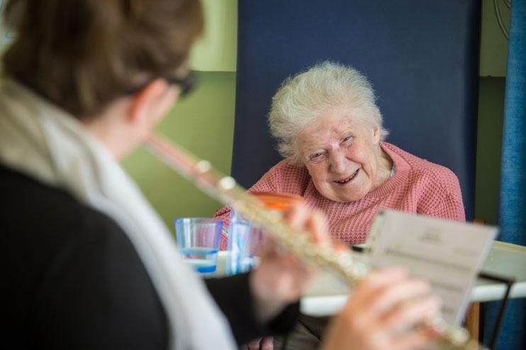 Alis Eaton plays the flute to hospital patient Ivy