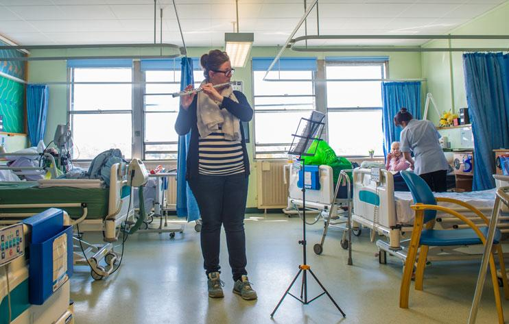 Alis Eaton plays the flute to hospital patients