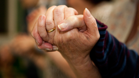 Person with dementia holding hands with their carer