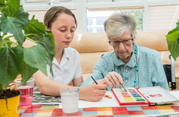 A pupil and person with dementia paint together at a Paint Pals party.