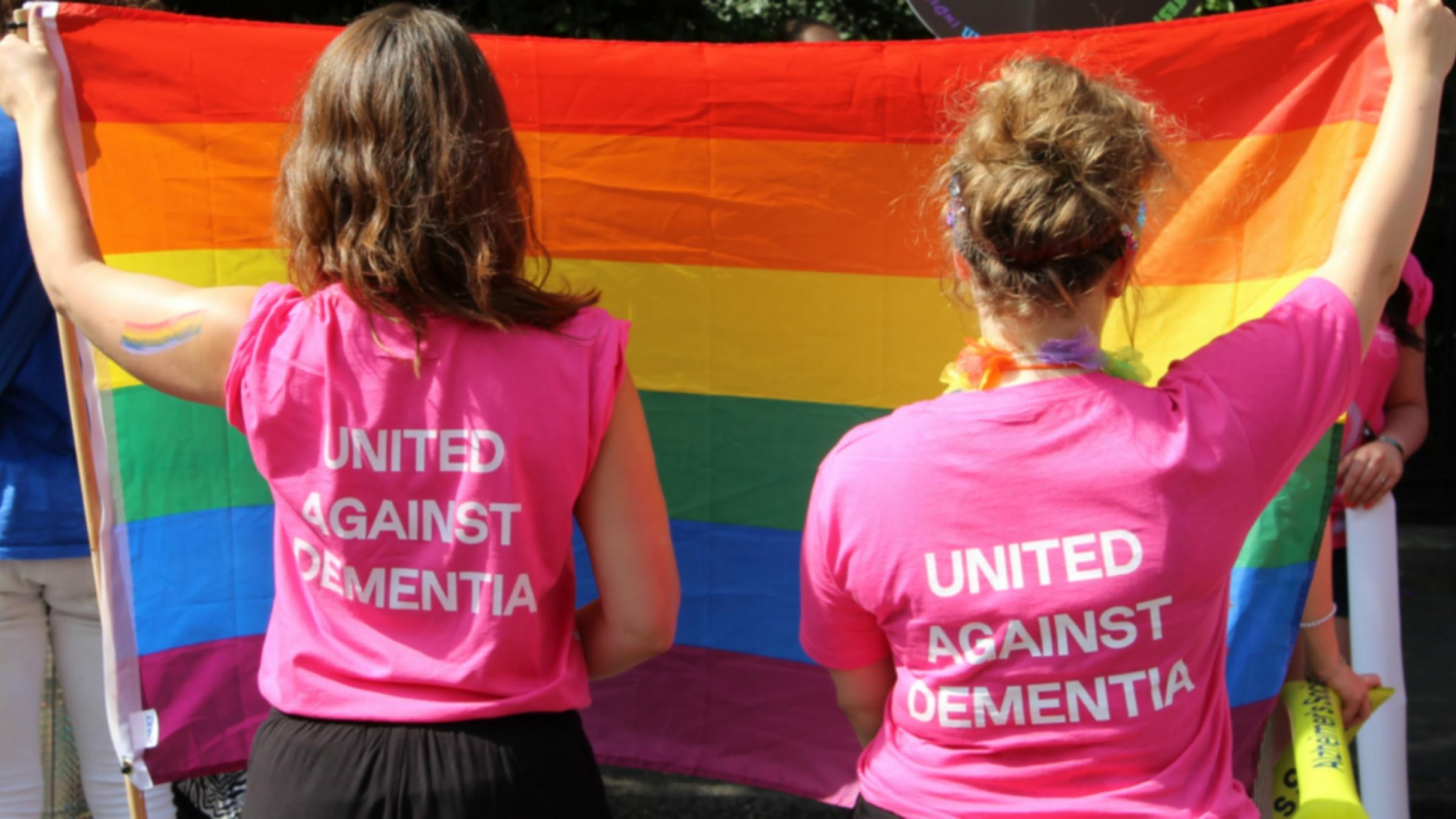 Two people holding LGBT flag wearing United Against Dementia T-shirts