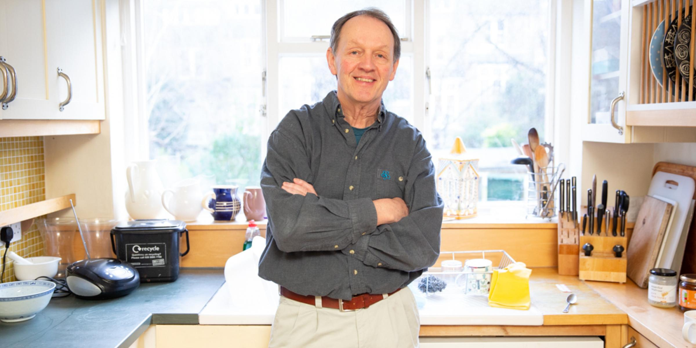 Kevin Whately smiling in his kitchen with his arms folded