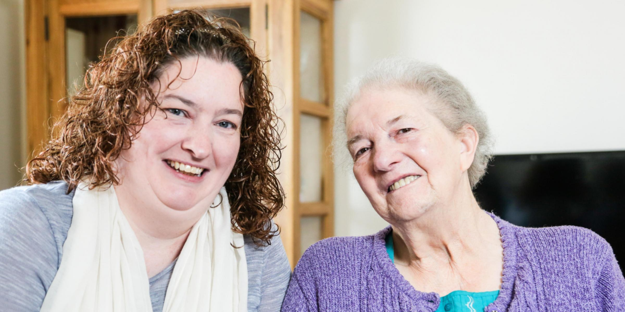 A carer smiling with a person with dementia
