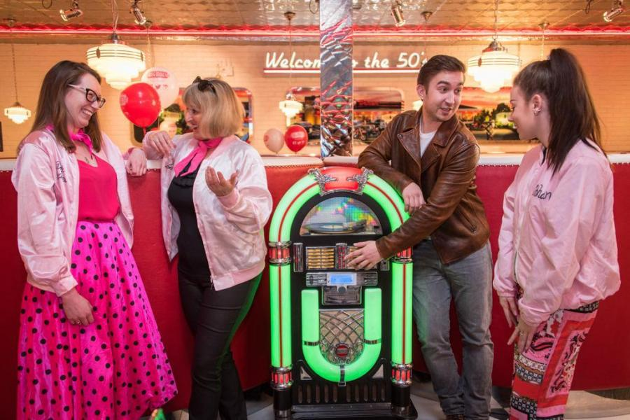 Four Flashback fundraisers crowd around the jukebox