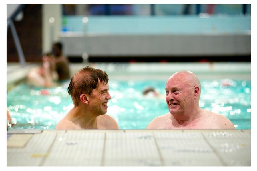 A person with dementia and a volunteer go swimming