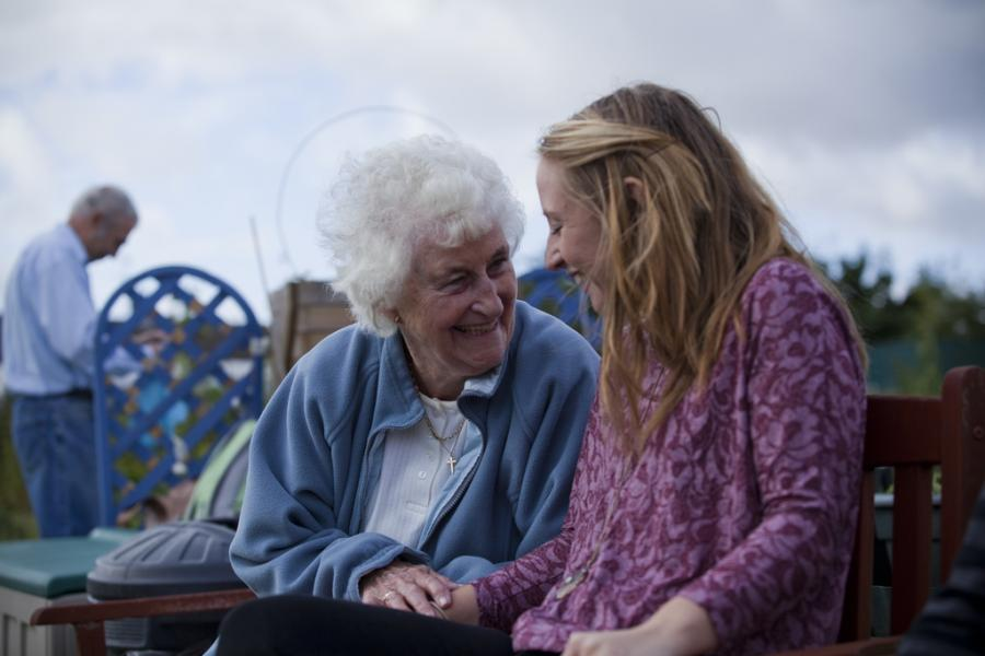 A volunteer sits on a park bench alongside a person with dementia