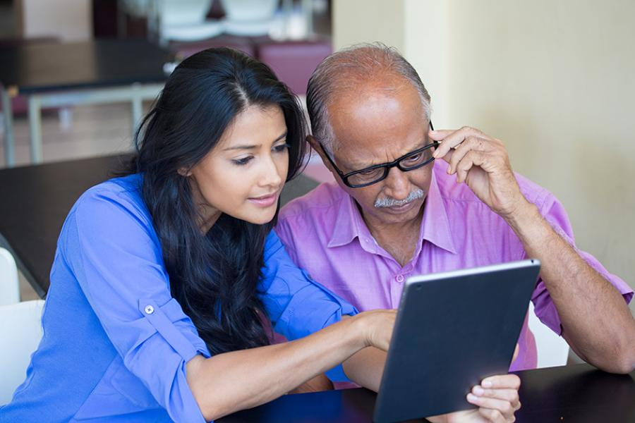 A middle-aged woman and older man look at information on a tablet computer
