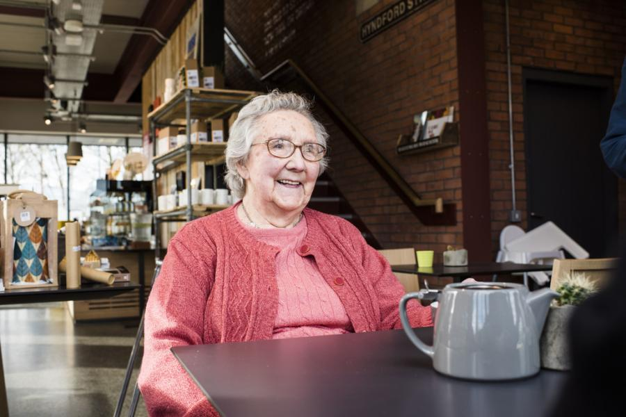 A woman with dementia sitting down in a cafe