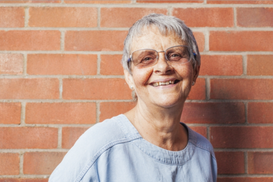 Wendy- living with dementia- standing against a brick wall