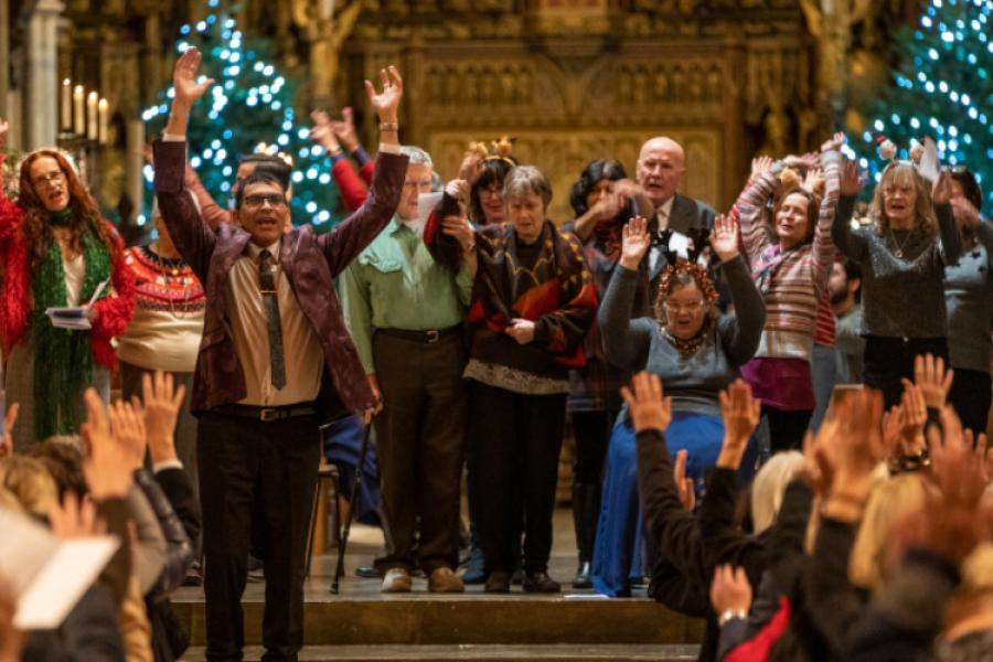 A carol service held in a place of worship with people on stage singing and with their arms in the air