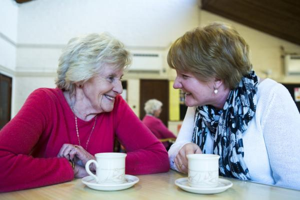 A person with dementia and a side by side volunteer visiting a cafe