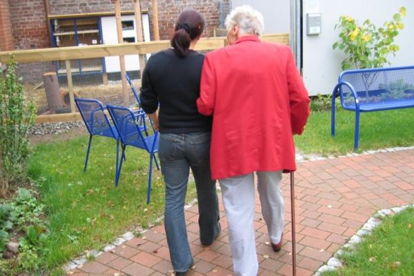 Care home staff walking with resident