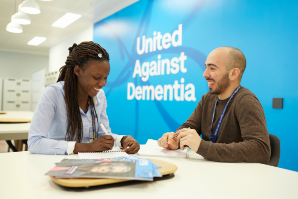 Two Alzheimer's Society employees having a meeting in front of wall that says 'United Against Dementia'
