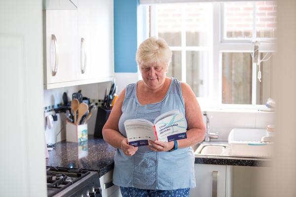 A person with dementia reads the Dementia Guide