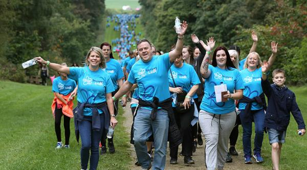 A large group of people walking wearing Alzheimer's Society branded Memory Walk t-shirts walk towards to viewer, a procession of people also part of this Memory Walk can be seen from the foreground to far into the background