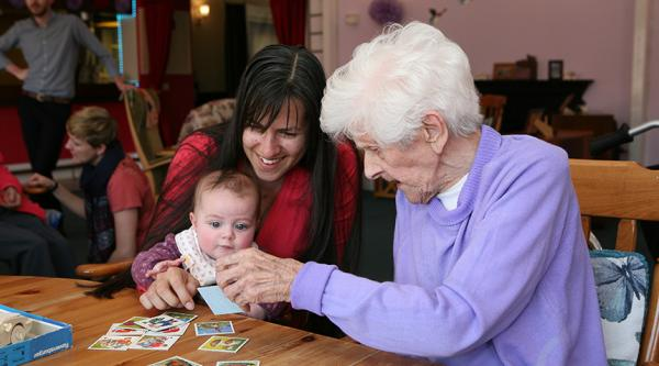 A resident interacts with a young child at a care home.