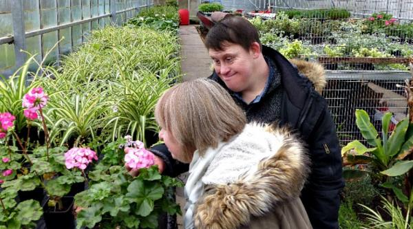 Couple with Down Syndrome smelling flowers