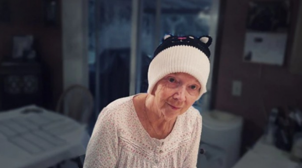 Woman living with dementia standing and looking at the camera