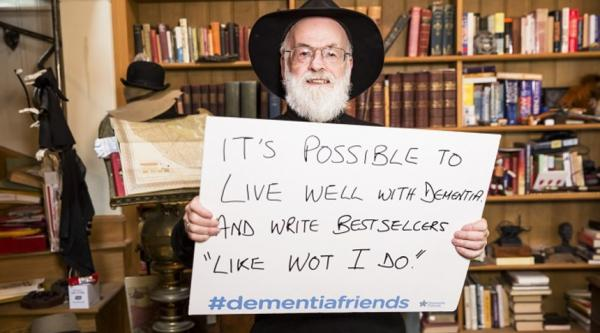 "Terry Pratchett holding a sign which reads: 'It's possible to live well with dementia and write bestsellers ""like wot I do""'"