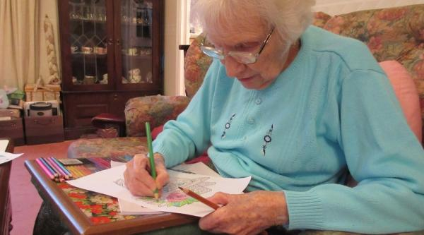 A woman with dementia sitting down and drawing