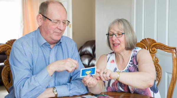 A person with dementia and their primary carer playing Monopoly