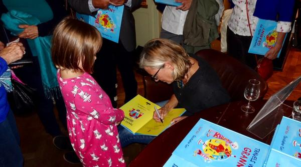 Author Juliet signs a copy of her book for a child