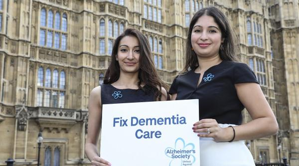 Campaigners hold a Fix Dementia Care sign outside parliament