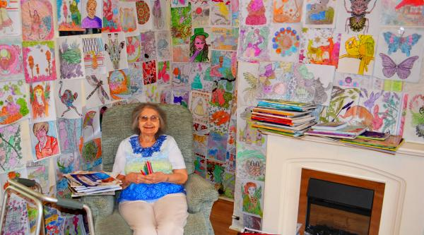 Woman sitting with her colouring artwork