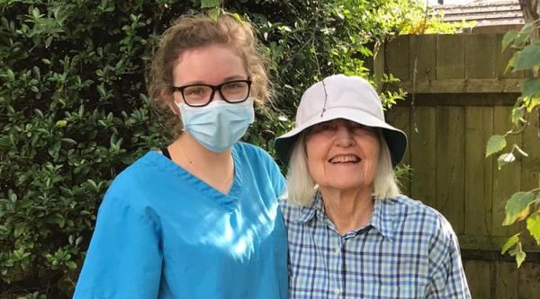 Ellie, a care home worker, wearing a face mask and standing beside a resident