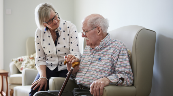 Woman looking lovingly at man sitting beside her in an armchair, holding a walking stick