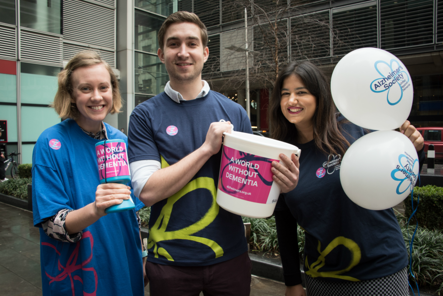 Three Alzheimer's Society fundraisers with balloons and bucket collections