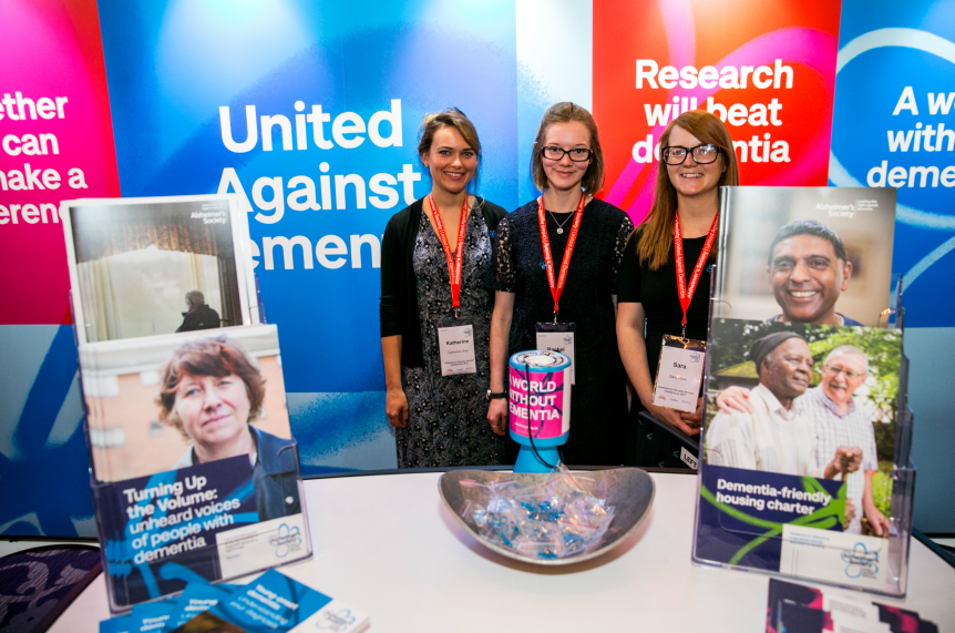 Three women at standing behind Alzheimer's Society stand