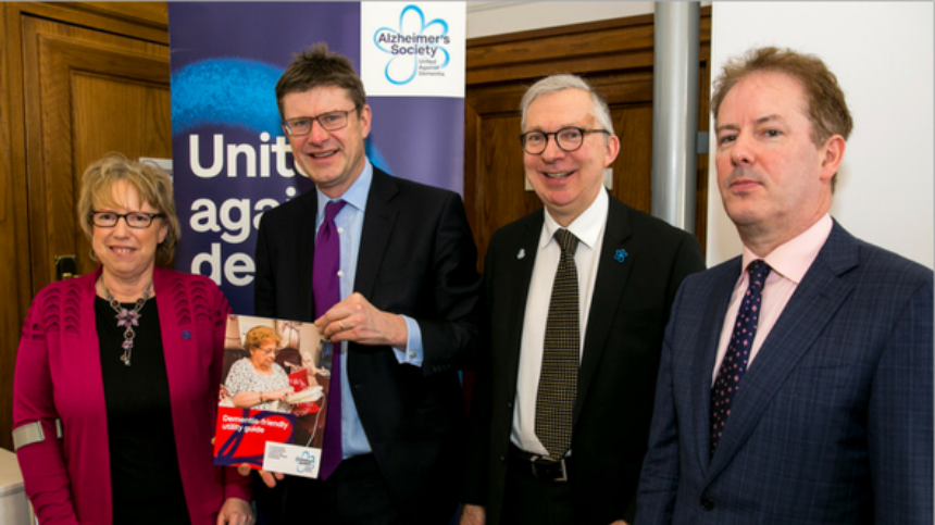 Four representatives in front of a 'united against dementia' banner