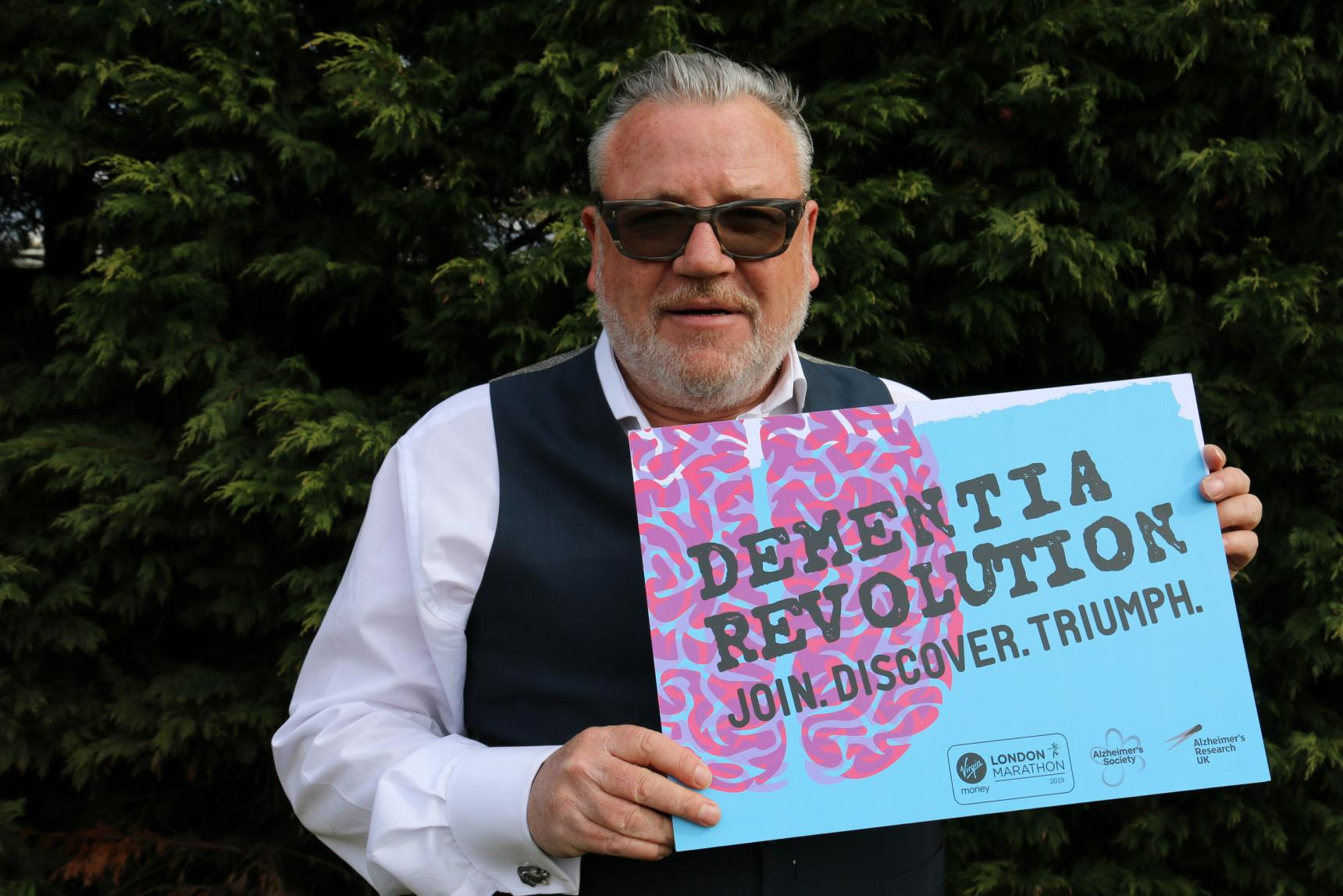 Ray Winstone holding a dementia revolution sign